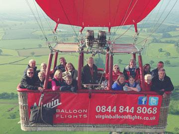 Hot air balloon with passengers inside mid-flight.