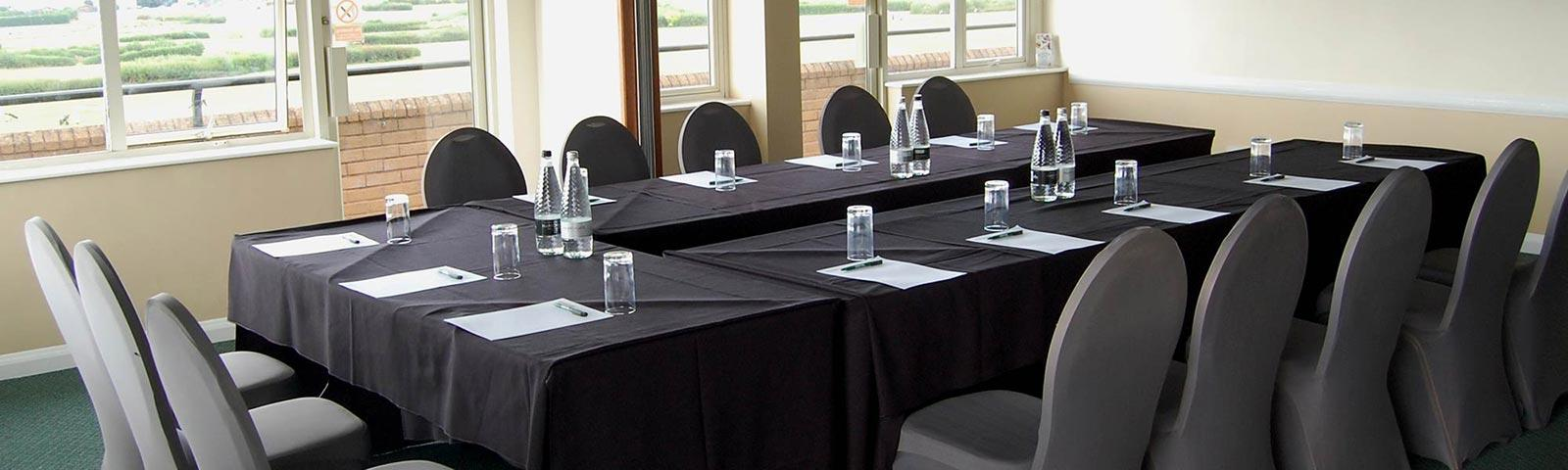 Meeting room set up with a table and chairs.
