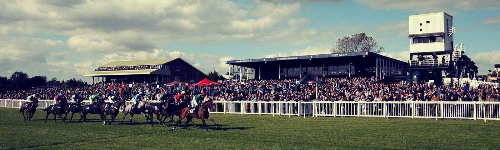 A raceday at Hereford Racecourse with crowds watching the jockeys race past.