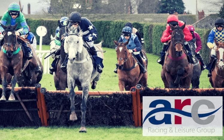 Jockeys jumping over a hurdle during a race at Hereford Racecourse.