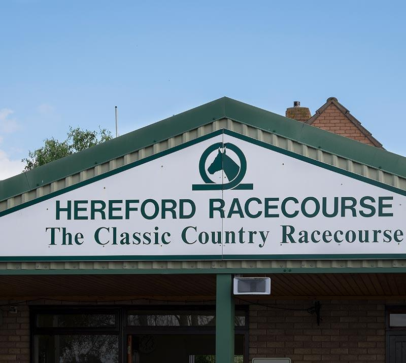 Close up on a entrance building to the Hereford Racecourse with the signage up on the wall.