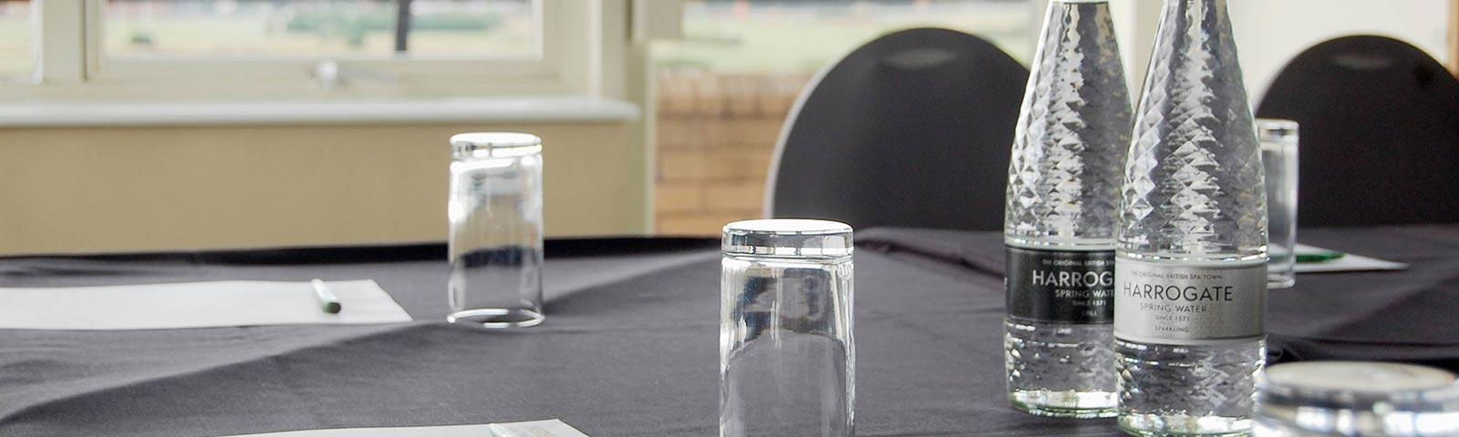 Close up on a table set up for a meeting with pens, paper, bottles of water.