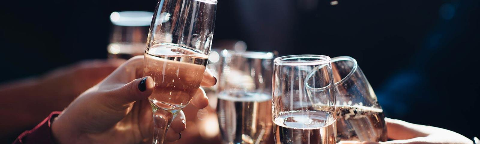 Close up on a few female hands holding champagne glasses.