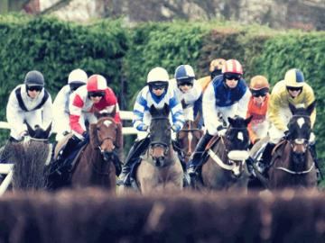 A group of jockeys racing at Hereford Racecourse.