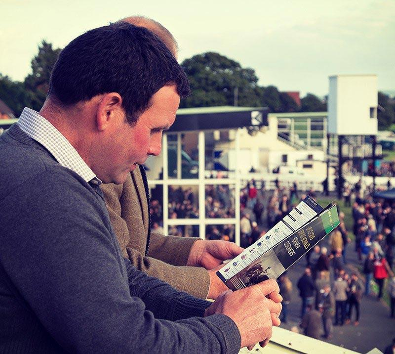 A man reading a racecard at the races.