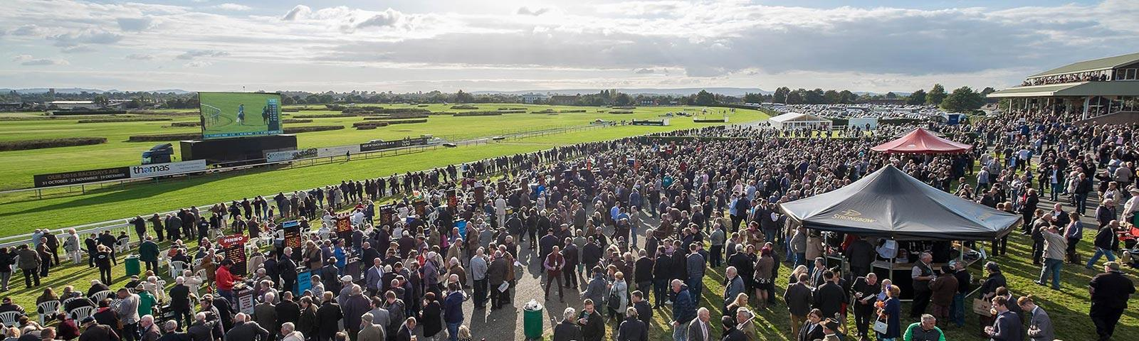 Crowds watching racing at Hereford Racecourse.
