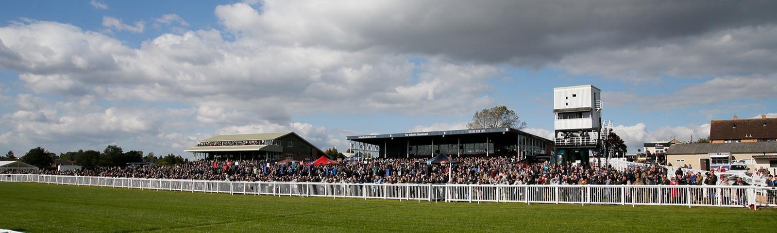 Crowds watching racing with the main Hereford Racecourse grandstand in the background.